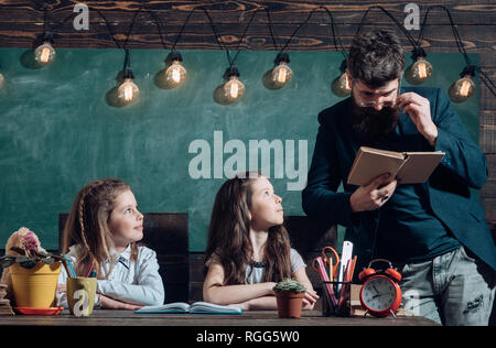 Educational concept - schoolchildren in a classroom. Enrichment classes can be difficult for some kids so tutors are best. Final exam test in - Stock Photo