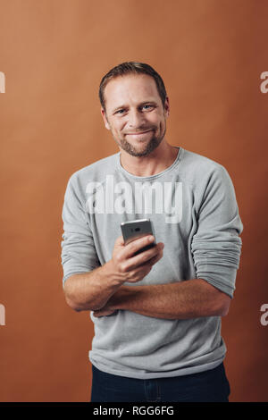 Half-length front portrait of smiling young man with smartphone in his hand, wearing grey long sleeve shirt and short haircut. Looking at camera with  - Stock Photo