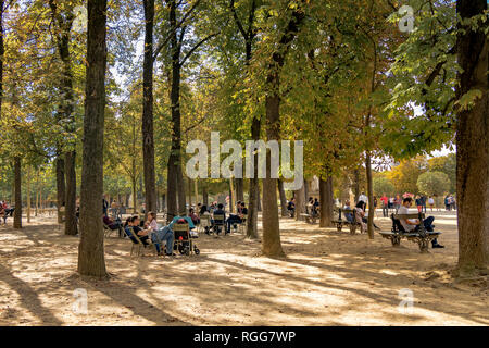 People sitting on benches and chairs in the shade of the trees on a hot summer's day in The Jardin du Luxembourg , Paris , France - Stock Photo