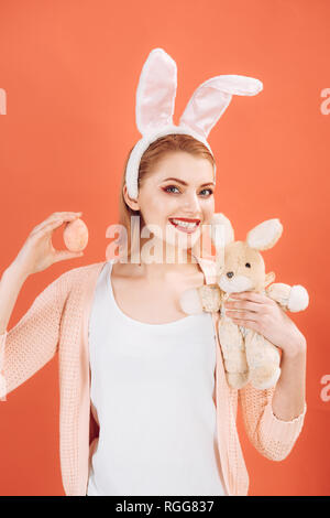 happy woman in bunny ears with toy. Woman in rabbit bunny ears. Happy easter. Spring holiday. Girl with hare toy. Egg hunt. Bunny with Easter eggs - Stock Photo