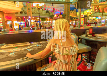 Back side of caucasian blonde woman gambling in casino with bright lights. Lifestyle girl waiting to play at blackjack in Las Vegas, Nevada, United - Stock Photo