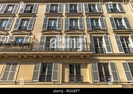White wooden shutters and wrought iron balcony  on an apartment building along Rue Saint-Dominique ,Paris,France - Stock Photo