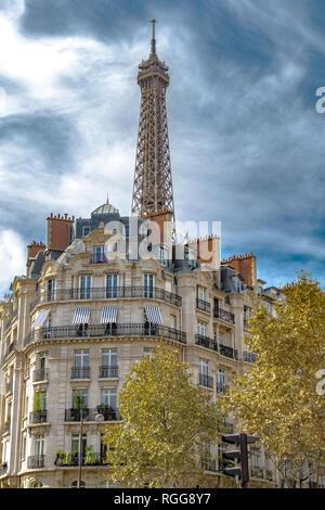 The Eiffel Tower rises above elegant Parisian apartment buildings with iron balconies in 7th arrondissement of Paris - Stock Photo