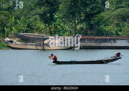 Vietnamese fisherman on a small boat fishing on the Perfume river in Hue, VIetnam, Asia - Stock Photo