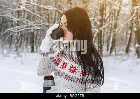 Woman drinks hot tea from thermos in the winter forest. Rest on the nature, travel, adventures - Stock Photo