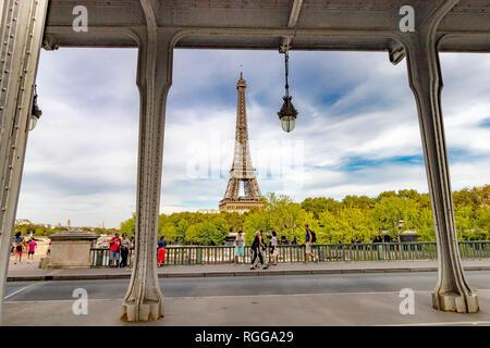 People walking across Pont de Bir-Hakeim with the Eiffel Tower in the distance , seen through the steel girders of Bir-Hakeim bridge,,Paris, France - Stock Photo