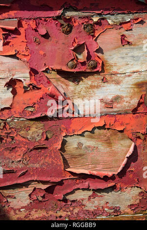 Detail of red paint peeling off an old wooden fishing boat, Ireland. - Stock Photo