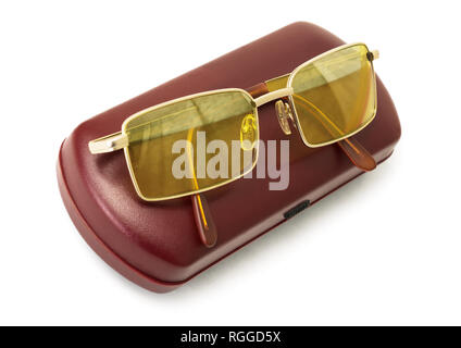 Anti-glare yellow glasses of driver on a red case on white background - Stock Photo