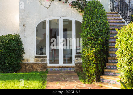 Beautiful exterior of newly built luxury home. Yard with green grass and walkway - Stock Photo