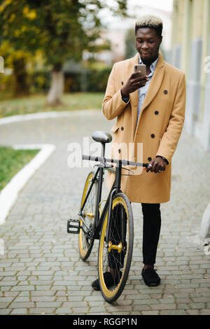 Portrait of handsome young man using mobile phone and fixed gear bicycle in the street.
