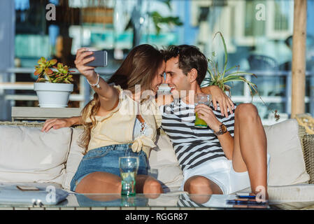 Happy affectionate young couple taking a selfie on the terrace of a bar - Stock Photo