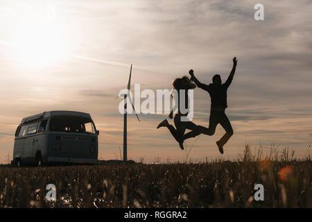 Exuberant couple jumping at camper van in rural landscape at dusk - Stock Photo