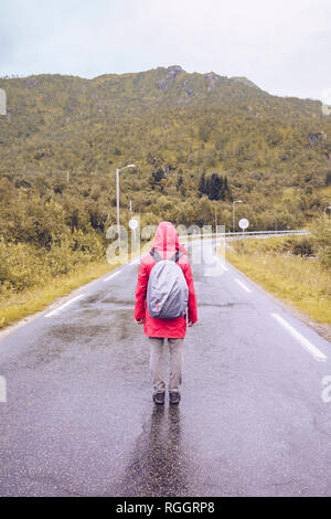 Norway, Lofoten, back view of man wearing red rain acket and backpack standing on wet road - Stock Photo