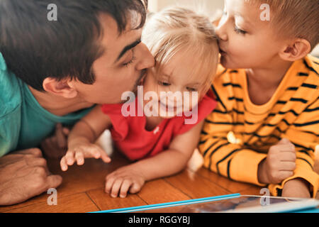 Father and brother kissing happy little girl - Stock Photo