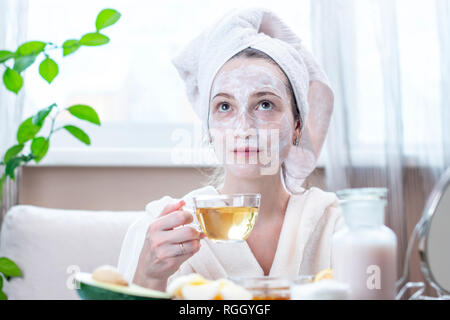 Beautiful happy young woman with natural cosmetic mask on her face. Concept skin care and Spa treatments at home - Stock Photo