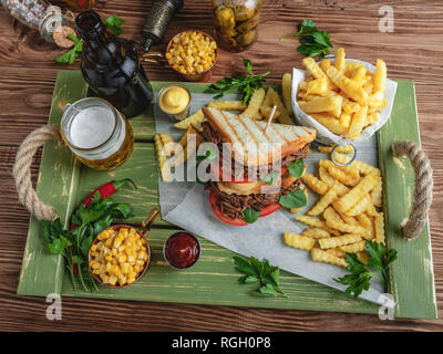 Sandwich beef pulled , barbeque, toast, french fries, sauce, corn on a wooden tray - Stock Photo