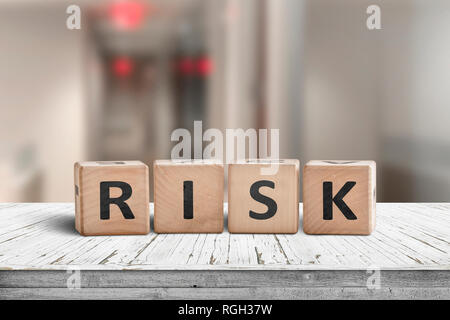 Risk sign on a wooden desk with red lights on in a hallway - Stock Photo