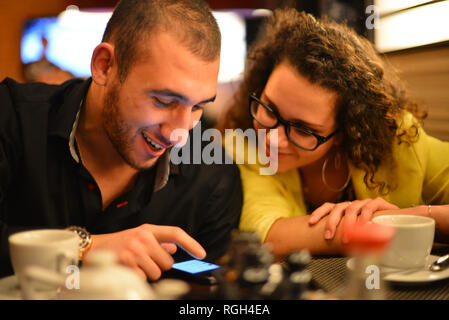 Guy and girl in the café. Guy is showing something fun to his girlfriend on his mobile phone screen. Both are happy and smiling. - Stock Photo