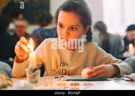 Lviv, UKRAINE - March 11, 2018. Little girl painting easter eggs. Traditionally, before Easter for centuries Ukrainian painted eggs. - Stock Photo