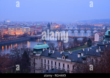 Bridges on Vltava river in winter. Charles bridge and Bridge tower in the middle. Late evening. View from Letna park. - Stock Photo