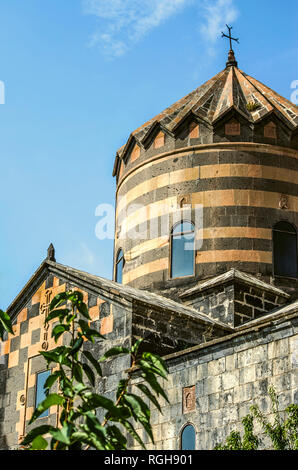 Facade wall with a relief cross under the roof and an umbrella dome with an iron cross in the monastery of St. George, Mughni village in Armenia - Stock Photo