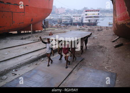 Workers carry a heavy piece of metal sheet at a Shipyard in Dhaka, Bangladesh on January 29, 2019. Dozens dockyards occupying 30.96 acres of the Buriganga foreshore have been in operation for the last 50 years. It is mostly utilized for fixing and repairing old ships, build in new ships. Labors work in the dockyard without helmets, face mask, or safety shoes as their ages from 8 to 80 years old. © Rehman Asad / Alamy Stock Photo - Stock Photo