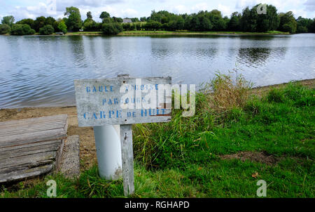 Dathee lake, Lac de la Dathee, popular place for fishing, yacht and golf in Normandy, France. On the board marked the place of night fishing the carp - Stock Photo