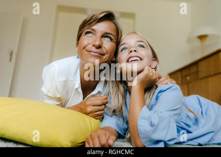 Happy mother and daughter lying on the floor at home watching something - Stock Photo