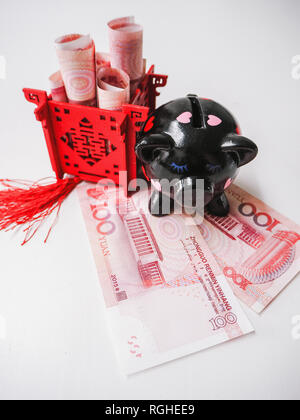 Black piggy bank and Chinese pavilion filled with banknotes, standing on Chinese 100 renminbi notes against a white background.
