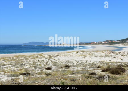 Beach with vegetation in sand dunes and lighthouse. Blue sea with waves and foam, sunny day. Galicia, Spain. - Stock Photo