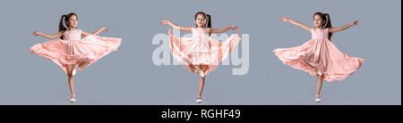 little girl in pink dress posing on gray background. - Stock Photo