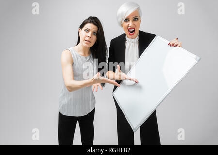 Portrait of two ferocious women with white blank magnetic Board in hands isolated on white background. A place for a label - Stock Photo