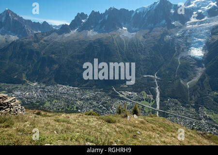 View looking down steep mountain-side to Chamonix, France taken from trails forming part of 'Tour du Mont Blanc'. Mont Blanc massif itself is visible. - Stock Photo