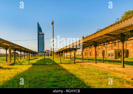 Abandoned old train station with contemporary tower building at background in aguada district, Montevideo, Uruguay - Stock Photo