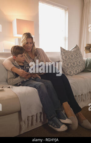 Side view of attractive mother with her son spending time together while reading story book in living room at home - Stock Photo