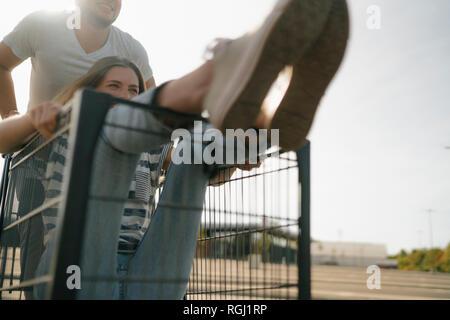Carefree young man pushing girlfriend in a shopping cart - Stock Photo