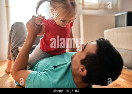 Little girl playing with her father at home - Stock Photo