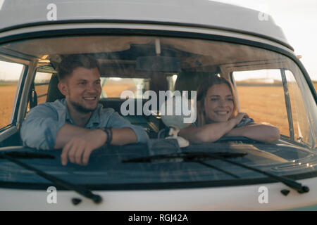 Happy young couple on a trip in camper van - Stock Photo