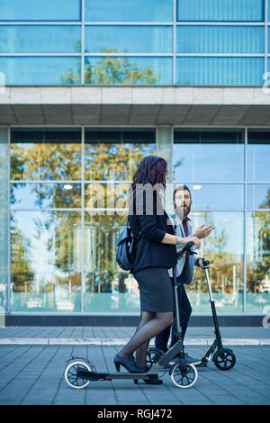 Businessman and businesswoman with scooters talking on pavement - Stock Photo