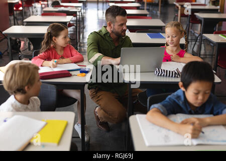 Front view of young school teacher helping girl with study on laptop in classroom - Stock Photo