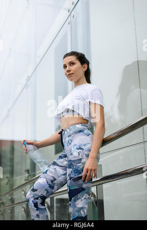 Fit young woman in the city holding water bottle - Stock Photo