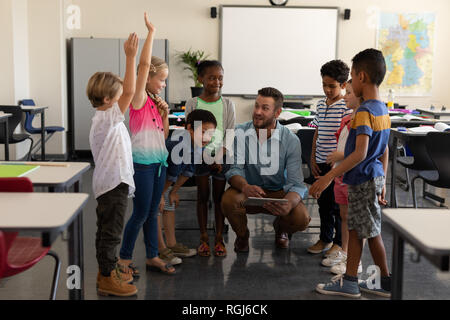 Front view of school kids raising hands while teacher teaching in classroom of elementary school - Stock Photo