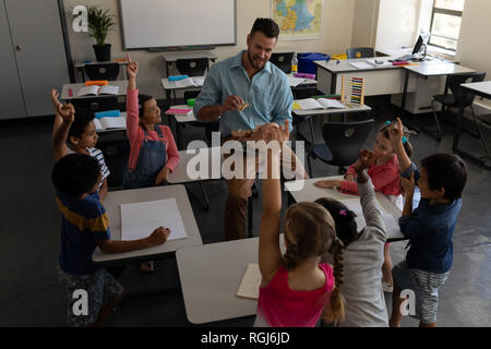 High angle view of school kids raising hands while teacher studying in classroom of elementary school - Stock Photo