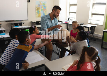 Male teacher teaching his kids about geography by using globe in classroom of elementary school - Stock Photo