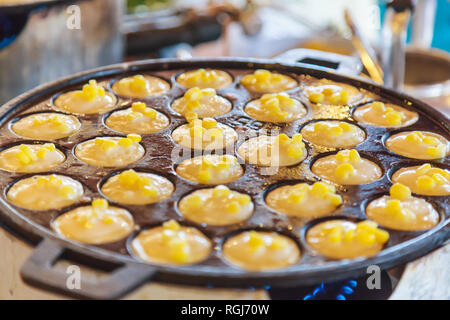 Khanom Khrok (coconut rice pancake), Traditional Thai Pudding Pancake Dessert, prepared by mixing rice flour, sugar, and coconut milk to form dough co - Stock Photo