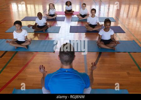 High angle view of yoga teacher teaching yoga to school kids in school gymnast - Stock Photo