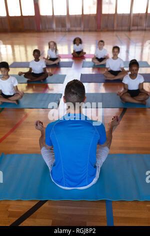 High angle view of yoga teacher teaching yoga to school kids in school - Stock Photo