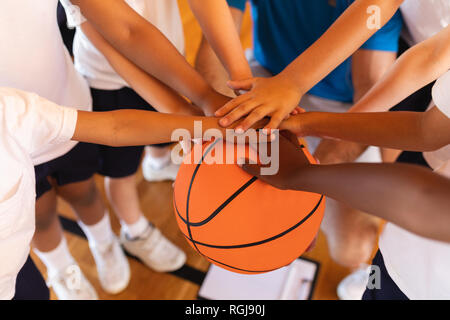 Close-up of Schoolkids forming hand stack on basketball at basketball court in school