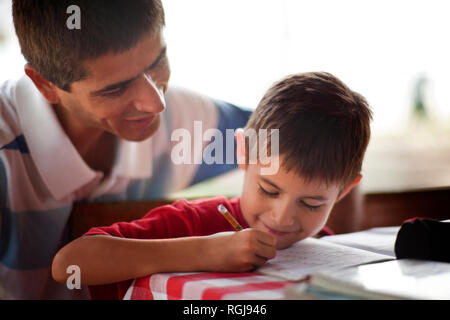 Father helping his son with his homework on a table. - Stock Photo