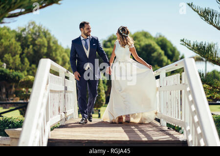 Bridal couple enjoying their wedding day in a park - Stock Photo